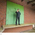 mann mittleren alters vor grünem rolltor und laderampe eines lagerhauses verweigert mit einer Geste (ausgestrecktehand) den zugang